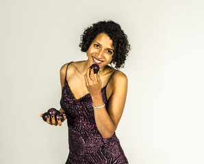 Young girl in a beautiful mulatto brilliant dress eating a plum