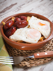 Eggs with french fries and small sausages