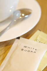 White sugar paper pack beside a cup of coffee