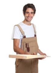 Lachender Schreiner mit Holzbrett