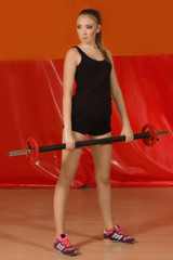 sports woman doing exercises with barbell in the gym