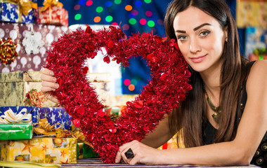 young brunet with red heart at holiday background