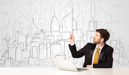 Businessman sitting at the white table with hand drawn buildings