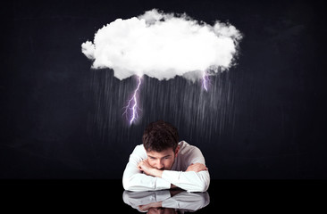 Depressed businessman sitting under a cloud