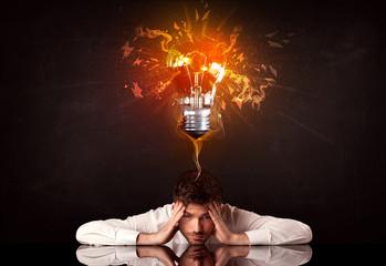 Businessman sitting under a blowing idea bulb