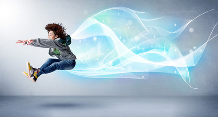 Cute teenager jumping with abstract blue scarf around her