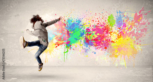 Leinwandbild Motiv Happy teenager jumping with colorful ink splatter on urban backg