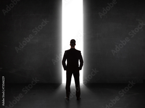 Leinwandbild Motiv Business person looking at wall with light tunnel opening