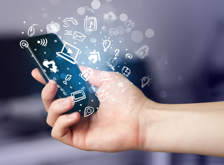 Hand holding smartphone with media icons and symbol