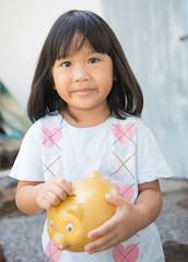 little girl saving money in a piggybank