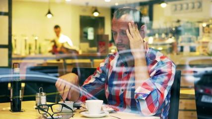 Man having headache and sitting in the restaurant, steadycam