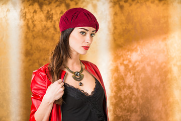 lovely lady portrait in red hat and jacket at golden background