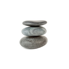 Three smooth stones on each other over white
