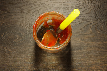 Messy tomato ketchup jar on the wooden floor