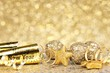 New Years Eve confetti and golden decorations on twinkling gold - 73576092