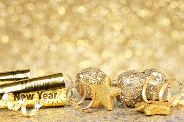 New Years Eve confetti and golden decorations on twinkling gold