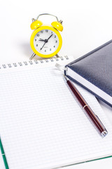 open notepad with pen and clock on white background