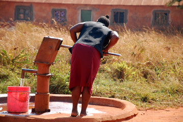 A woman and pump water from a public fountain-Pomerini-Tanzania-