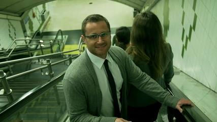 Businessman riding on escalator and smiling, steadycam shot