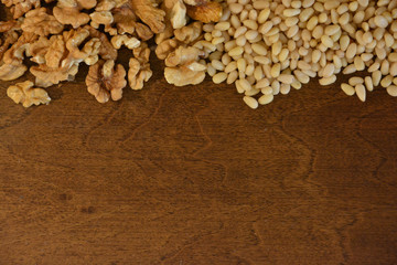 Walnuts and cedar pine nuts on wooden background