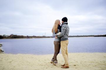 the guy and the girl walk on a desert autumn beach