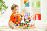 kid boy plays with educational toy indoor poster
