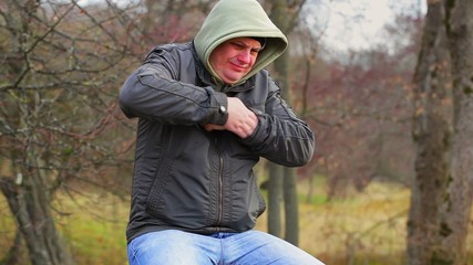 Man with itchy body at outdoors on the bench in the park