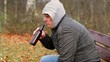 Man drink beer from bottle in the park on the bench