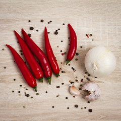 Жгучий перец с луком на деревянном фоне, Hot peppers and onions