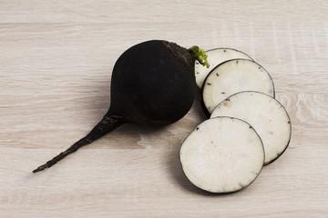 Черная редька на деревянном фоне, Black radish on a wooden backg