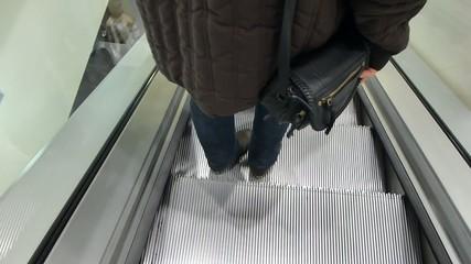 Female shopper on escalators in department store