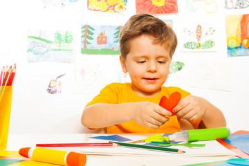 Happy small boy crafting heart shaped carton