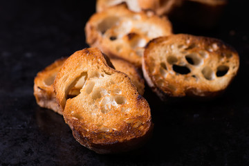 Toasted crusty baguette  on old black background