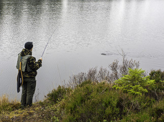 fly fisher man fighting fish