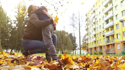 Little son brings autumnal leaves bouquet to his mom