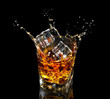 Glass of whiskey with splash on black background - 73585824