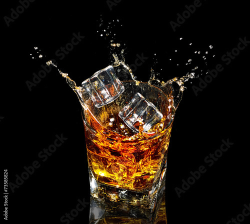 Fotobehang Alcohol Glass of whiskey with splash on black background