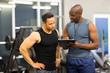 african personal trainer helping man to fill the membership form - 73586625
