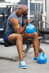 african man lifting kettle bell