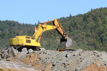 Large excavator loading articulating dump truck