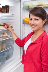Girl standing by the fridge