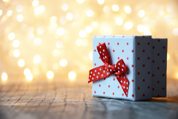 White gift box with red dots and bokeh background