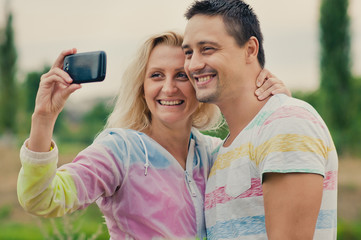 Couple fun taking self-portrait picture photos with mobile smart