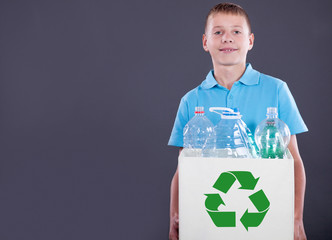 Recycling concept with young boy carrying recycling bin