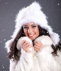 portrait of a beautiful young woman in a white fur coat over sno