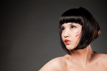 Young asian woman posing on grey background