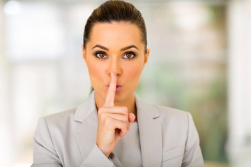young businesswoman saying shhh