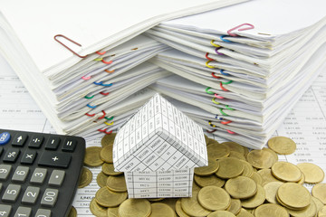 House on pile of gold coin with calculator