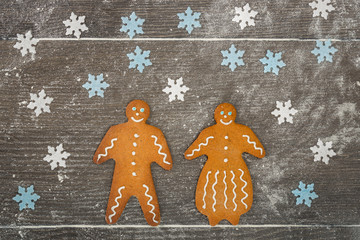 Gingerbread man and lady together on floury table.