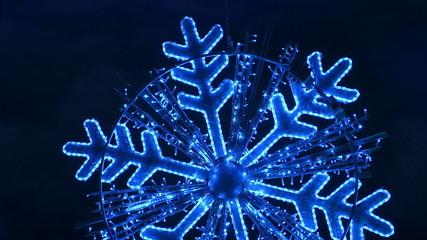 Illuminated new year snowflake on dark blue background